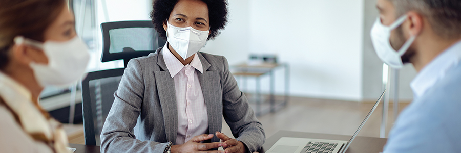 Female hospital administrator meeting with two medical staff, all wearing face masks in an office setting.