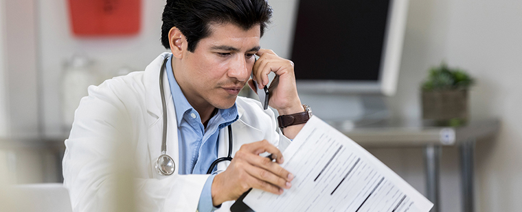 Male physician talks with colleague on the phone while reviewing a patient's chart.